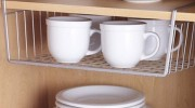 Under-shelf baskets are a great way to harness vertical space and add more storage. (Photo via ApartmentTherapy.com)